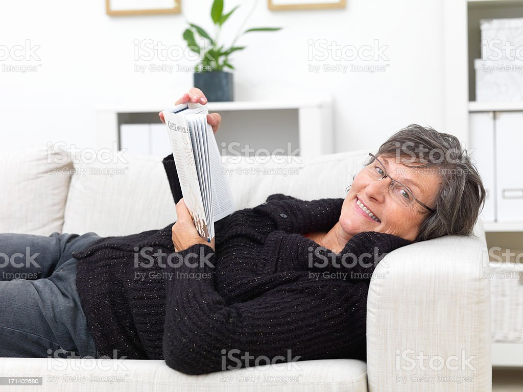 Happy mature woman lying on a sofa reading a book royalty-free stock photo