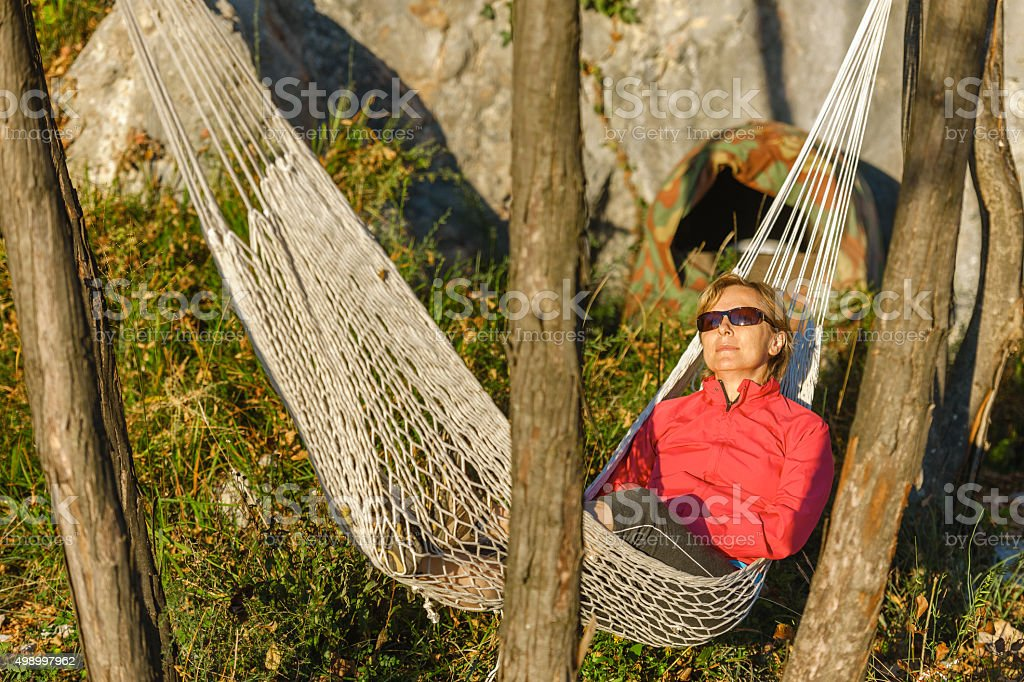 Happy Mature Woman Lying on Hammock in Wilderness at Sunset stock photo