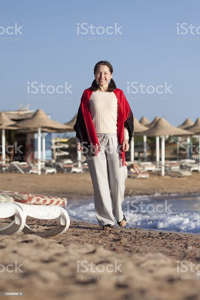 Happy mature woman on beach stock photo
