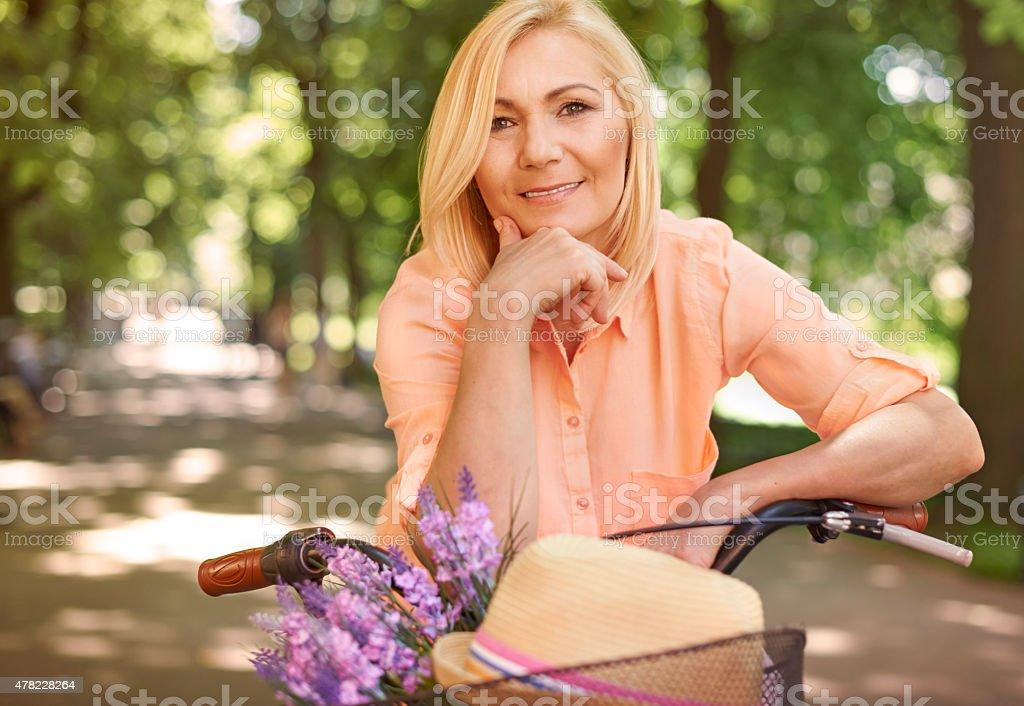 Happy mature woman on the bike stock photo