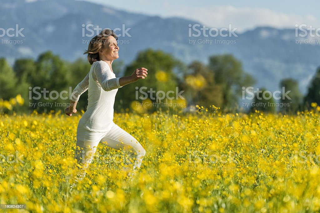 happy mature woman running in flower meadow stock photo