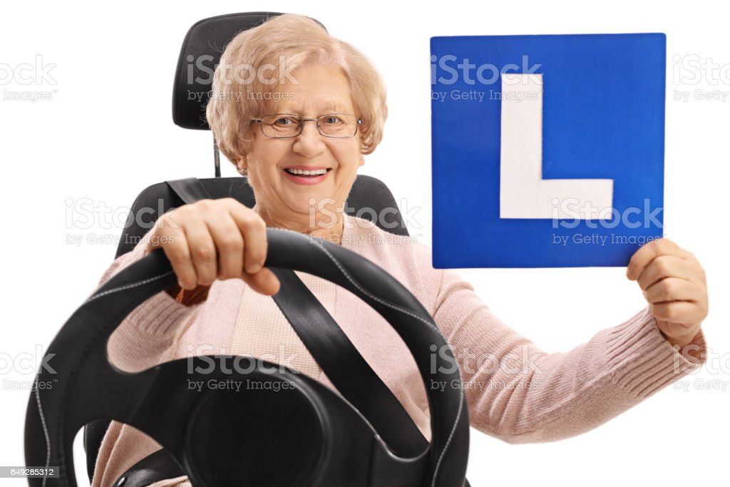 Happy mature woman sitting in a car seat and holding an L-sign stock photo