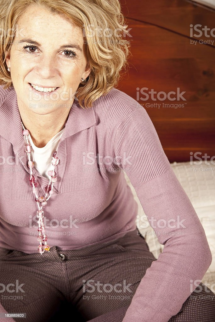 Happy Mature Woman Sitting On The Bed royalty-free stock photo