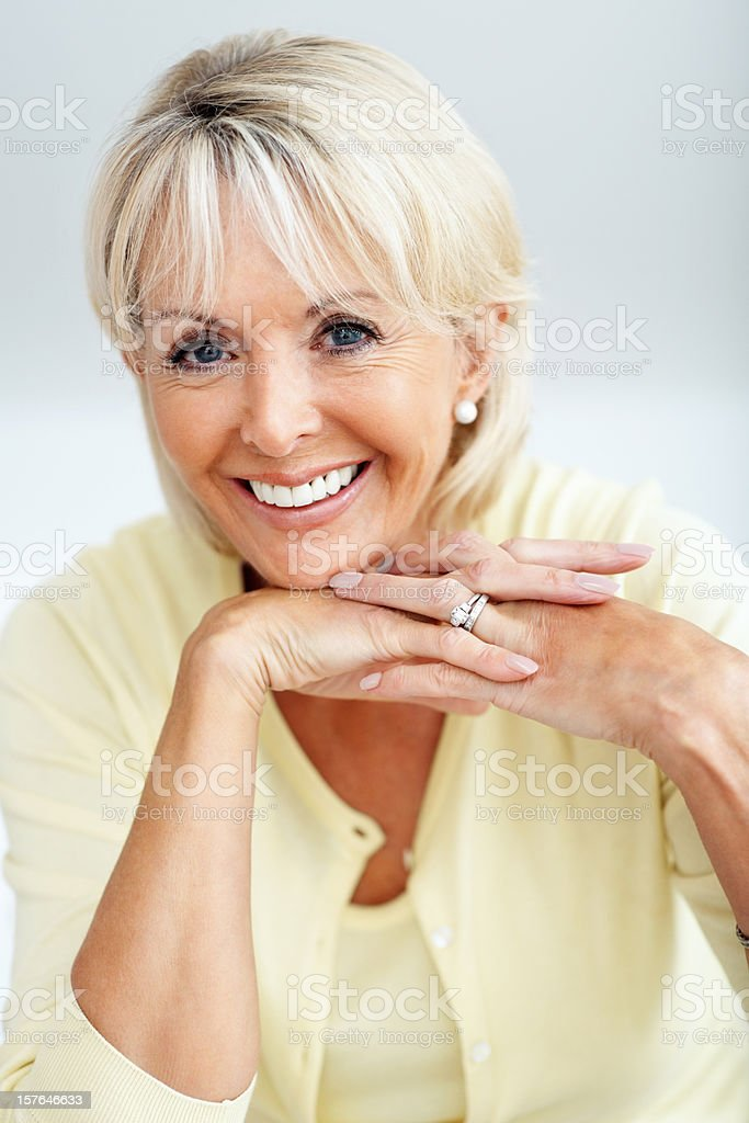Happy mature woman smiling with hands on chin royalty-free stock photo