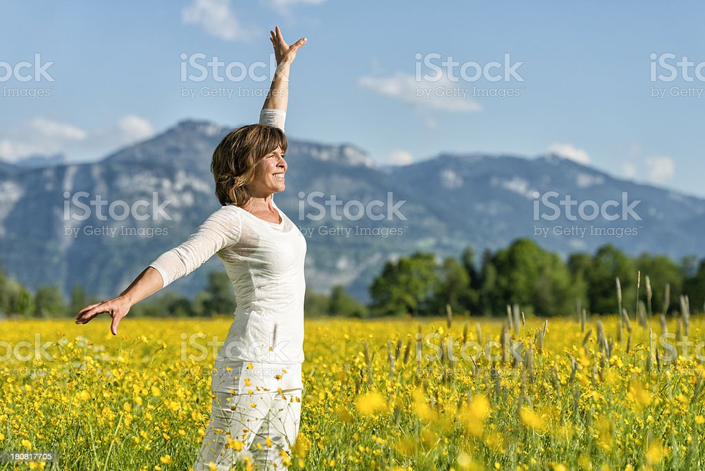happy mature woman standing in flower meadow royalty-free stock photo