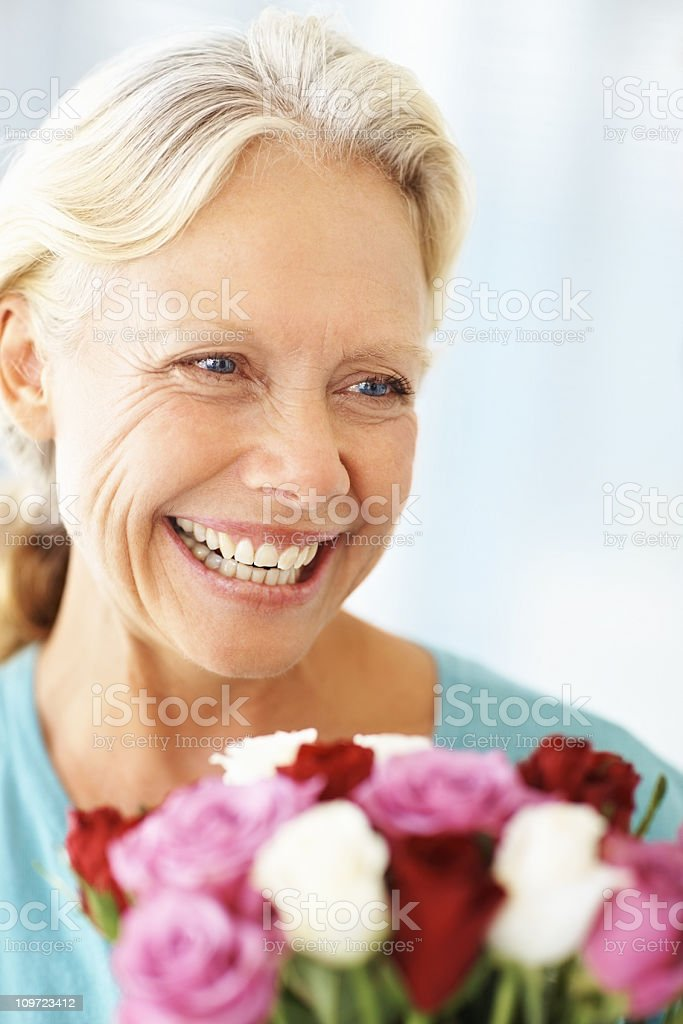 Happy mature woman with a bouquet of roses royalty-free stock photo