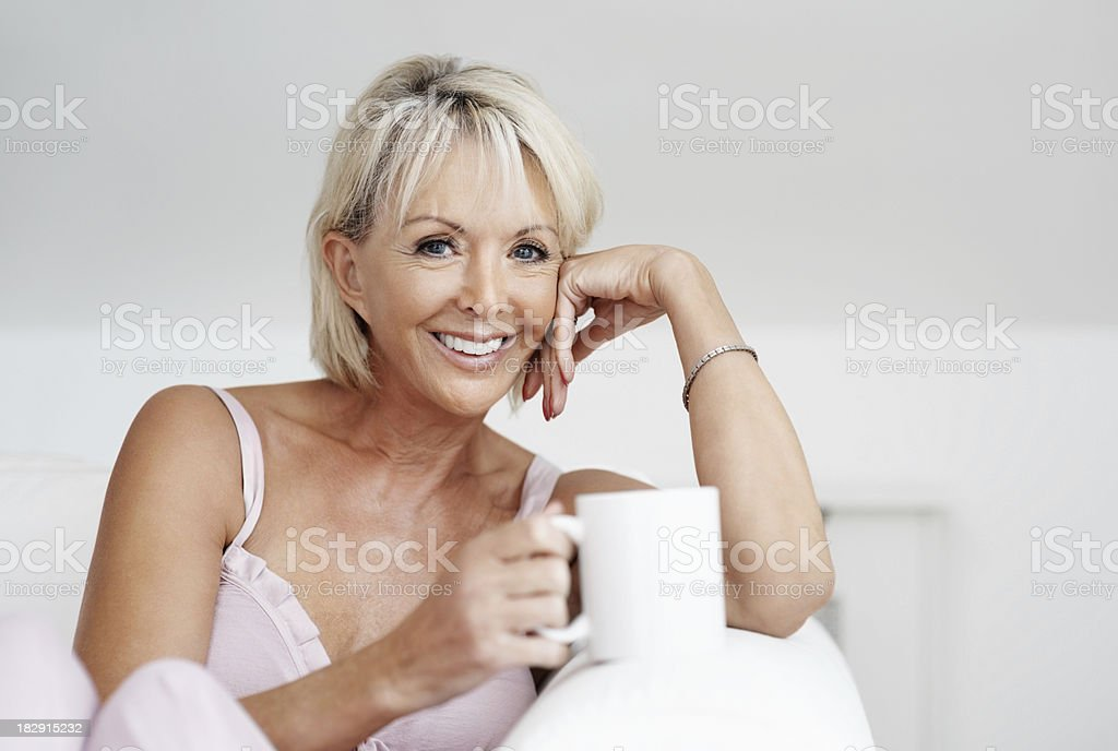 Happy mature woman with coffee cup at home royalty-free stock photo