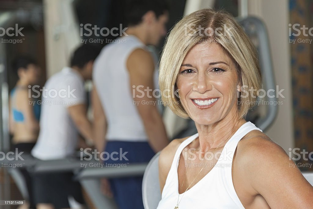 Happy mature woman working out in gym royalty-free stock photo
