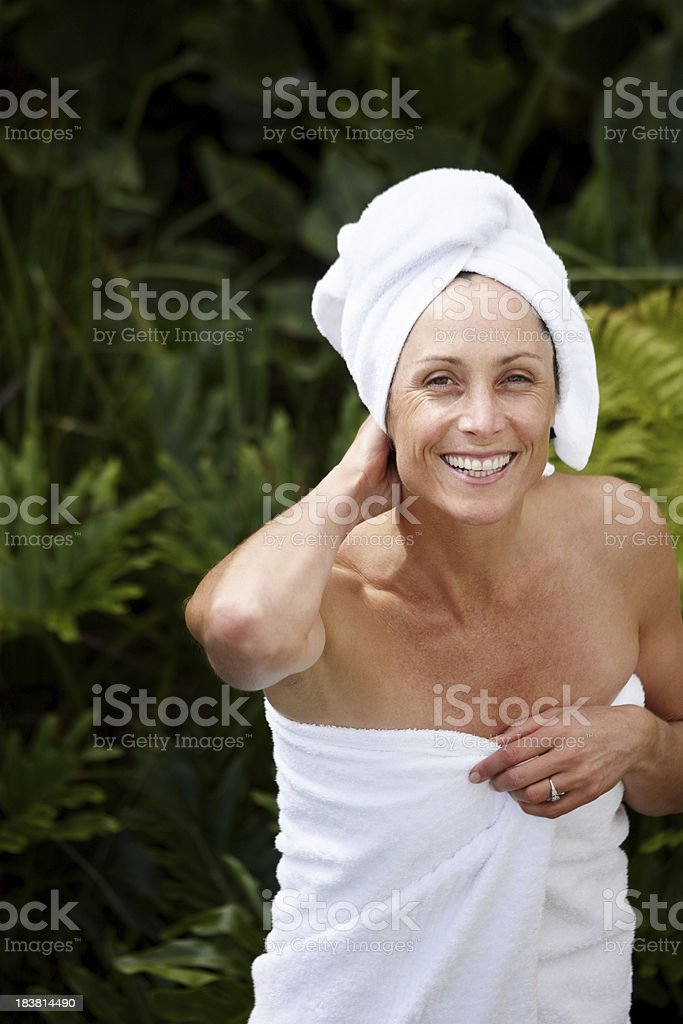 Happy mature woman wrapped in towel royalty-free stock photo