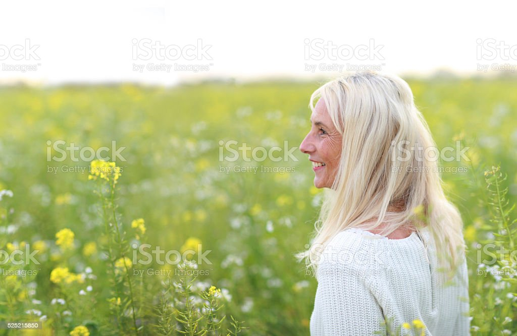 Happy matured woman in flowerfield stock photo