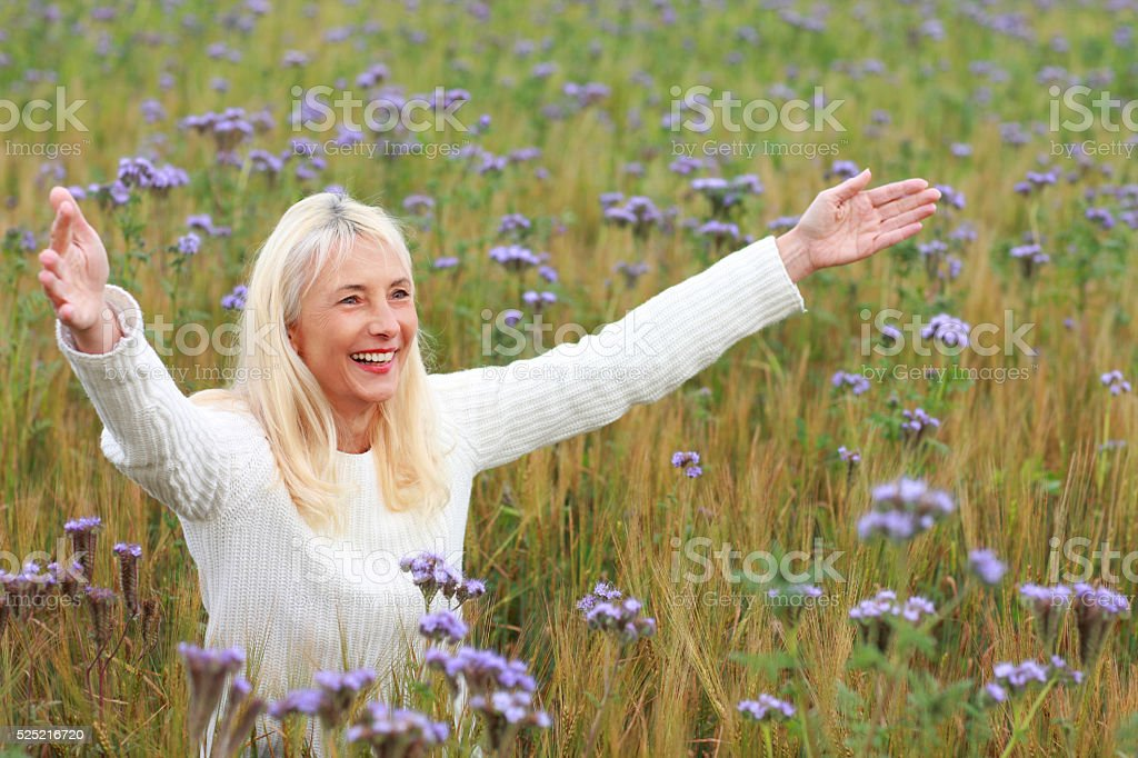 Happy matured woman with arms spread in flower field stock photo