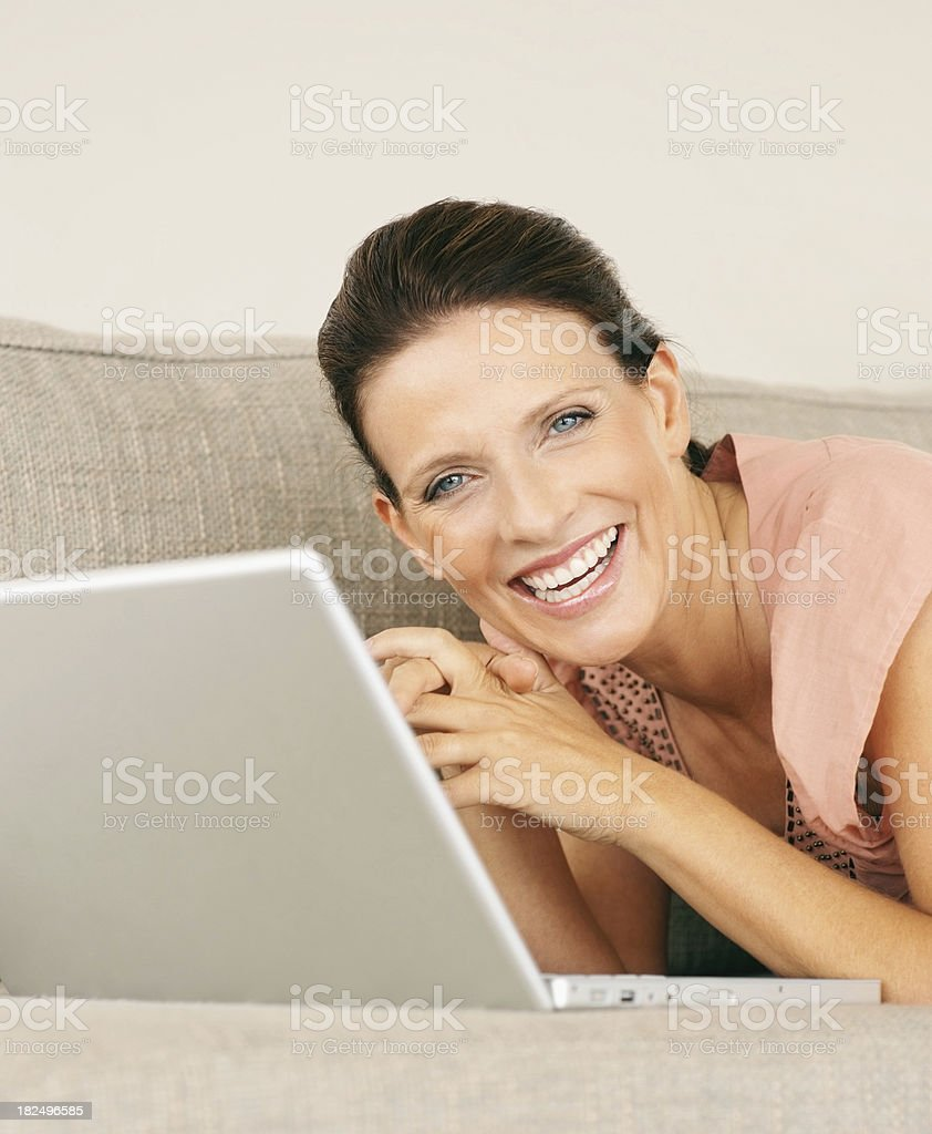 Happy maturewoman with a laptop lying on couch at home royalty-free stock photo