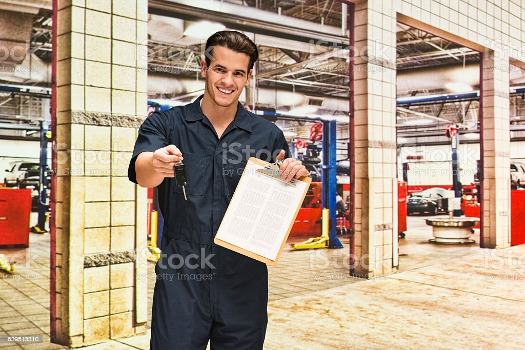 Happy mechanic holding car key in auto repair shop stock photo