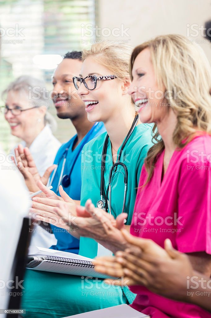Happy medical staff applaud after listening to speaker during conference stock photo