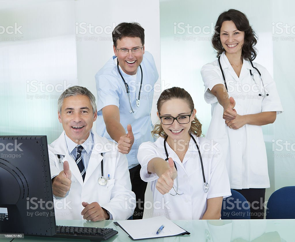 Happy medical team giving a thumbs up stock photo