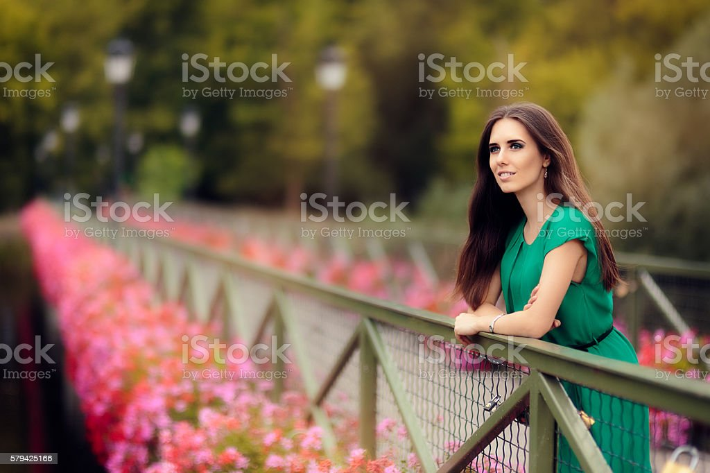 Happy Melancholic Woman on a Bridge with Flowers stock photo