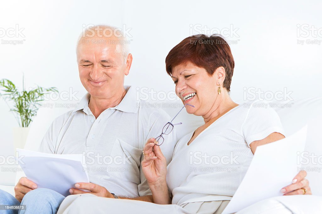 Happy Mid Adult Couple Doing Paperwork royalty-free stock photo