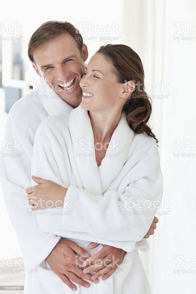 Happy mid adult couple embracing in bathrobe royalty-free stock photo