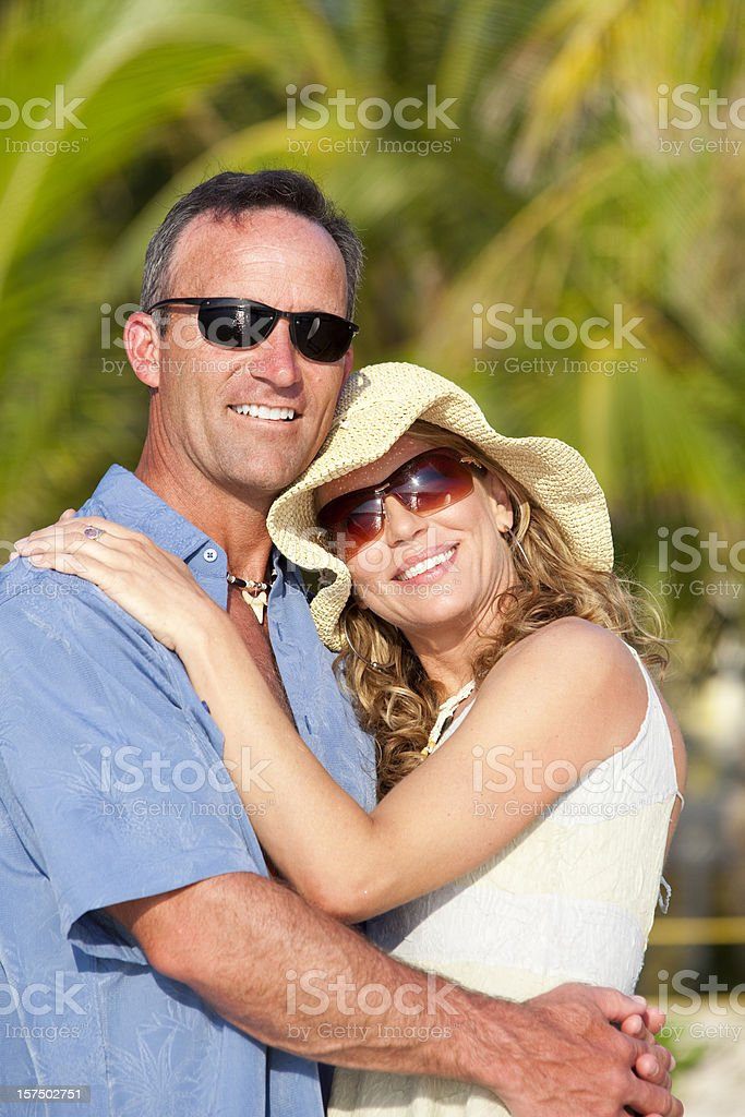 Happy mid adult couple embracing on beach royalty-free stock photo