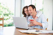 Happy mid adult couple looking at laptop at home