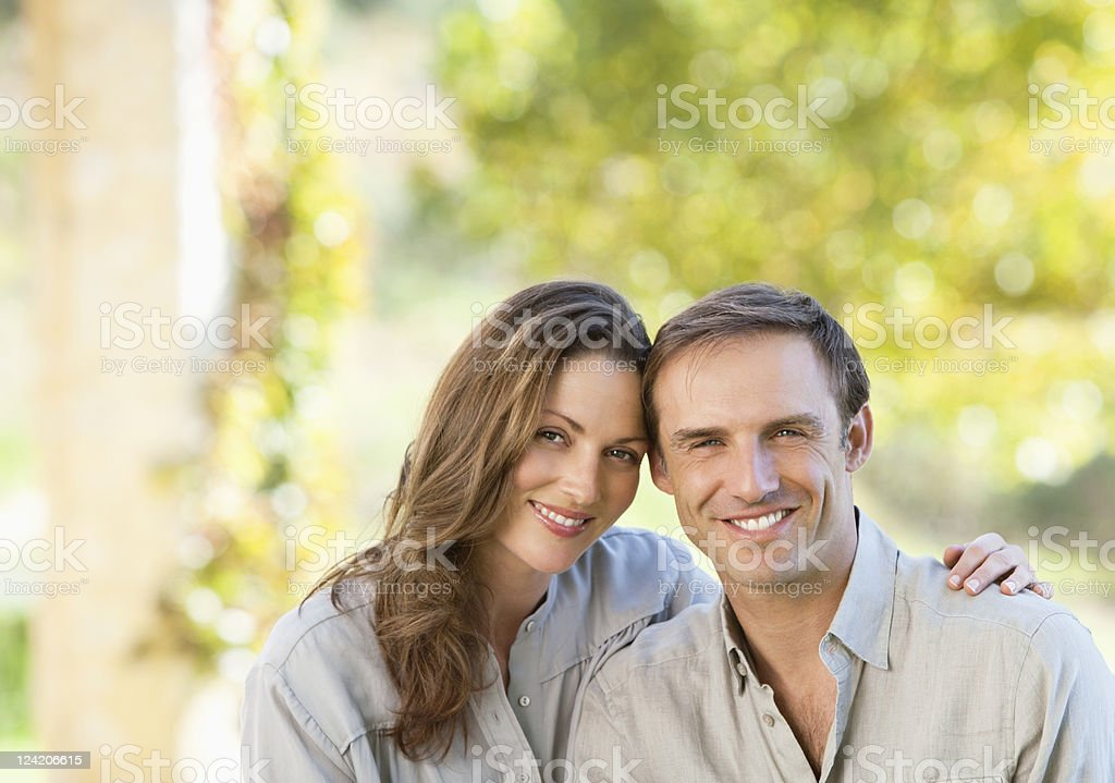 Happy mid adult couple sitting on bench in park stock photo