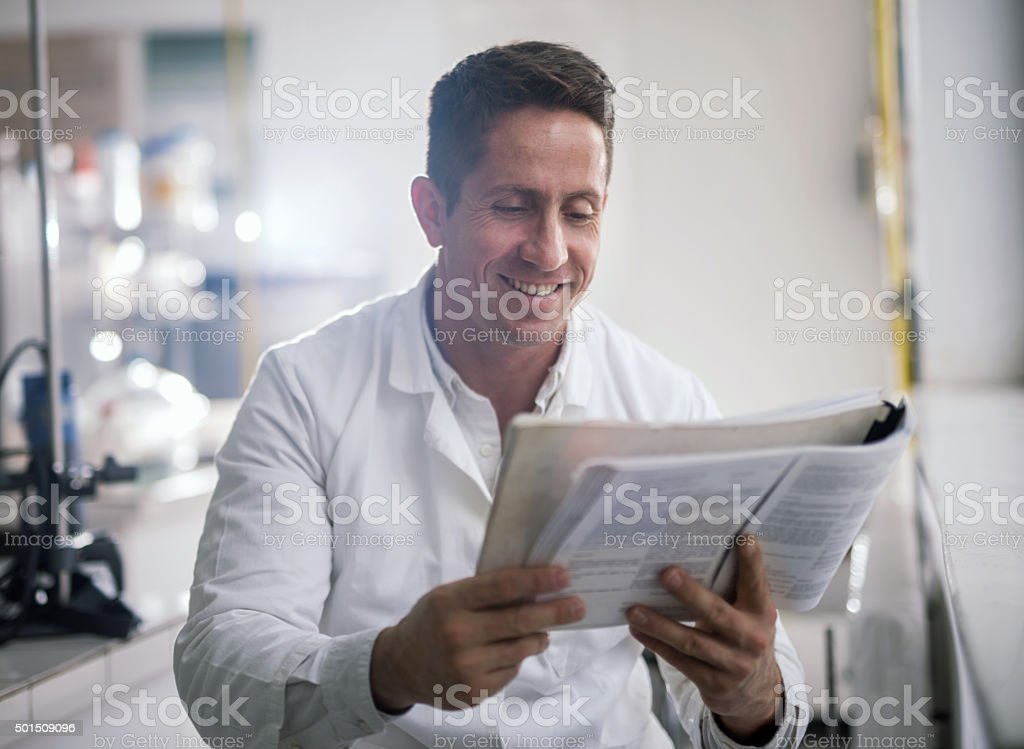 Happy mid adult doctor reading a medical book. stock photo