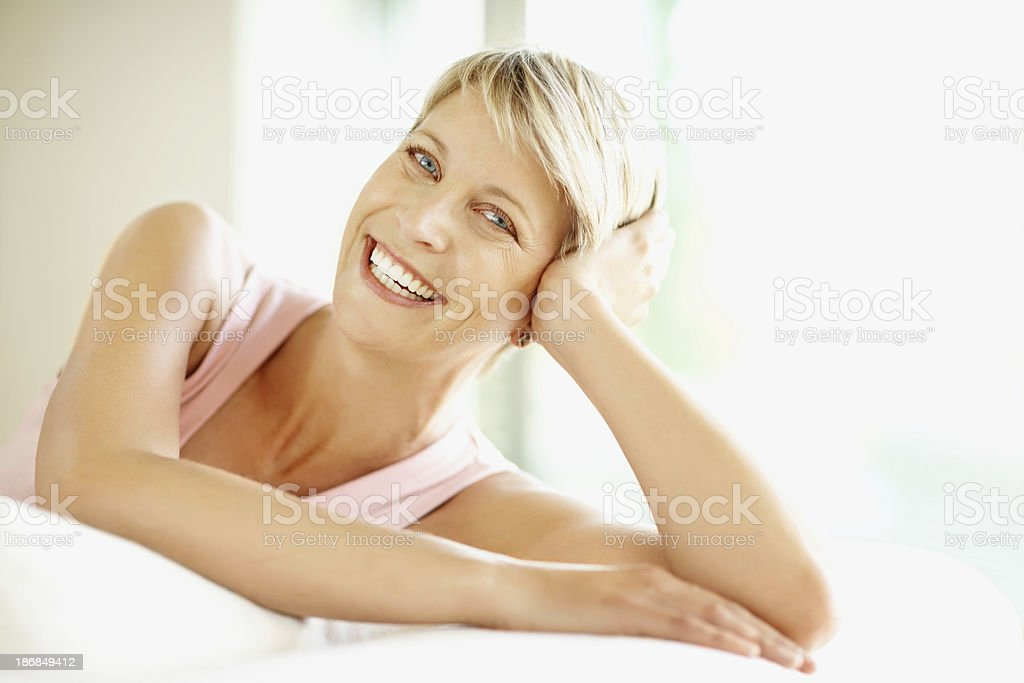 Happy mid adult lady relaxing on bed royalty-free stock photo