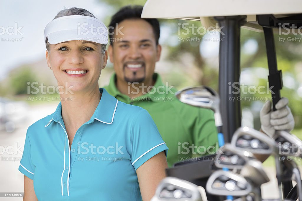 Happy mid adult woman standing near cart while playing golf royalty-free stock photo