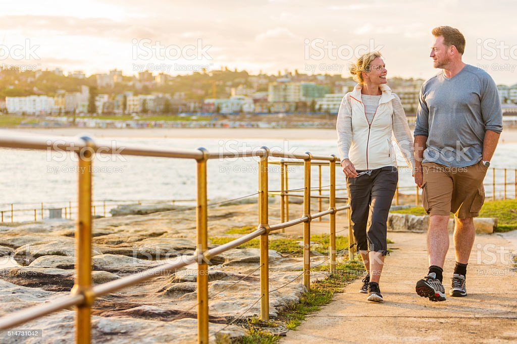 Happy Middle Aged Active Fit Healthy Beach Couple Walking Outdoors stock photo