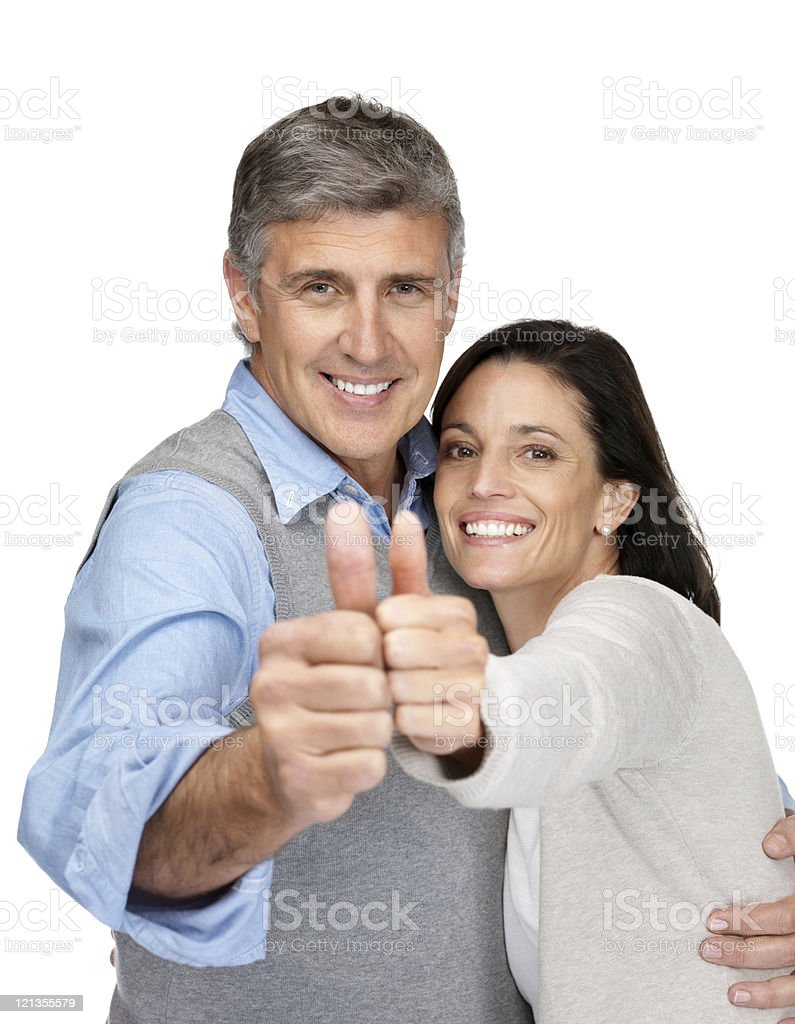 Happy middle aged couple giving thumbs up sign royalty-free stock photo