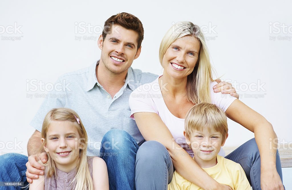 Happy middle aged couple sitting with their kids stock photo