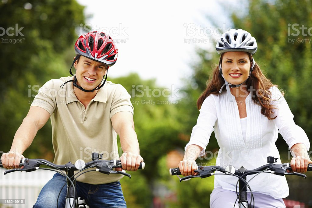 Happy middle aged couple wearing helmet while riding bicycles royalty-free stock photo