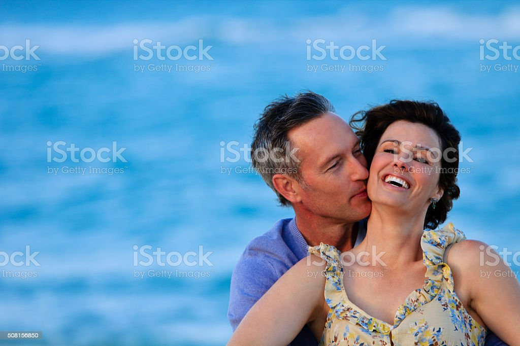 Happy middle aged woman enjoying a kiss on the neck stock photo