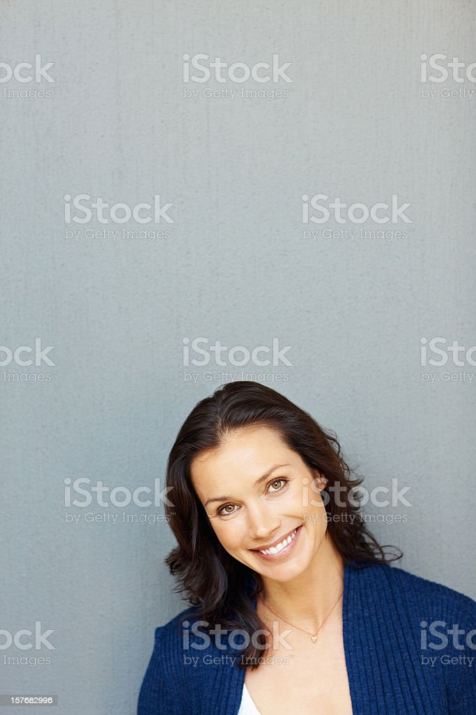 Happy middle aged woman smiling against plain background royalty-free stock photo