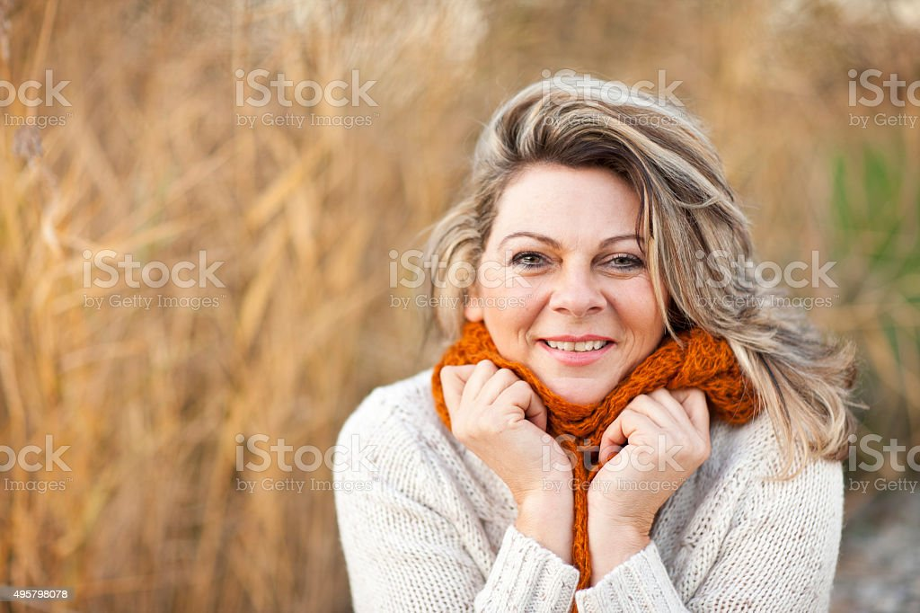 Happy middle aged woman with pullover and scarf stock photo