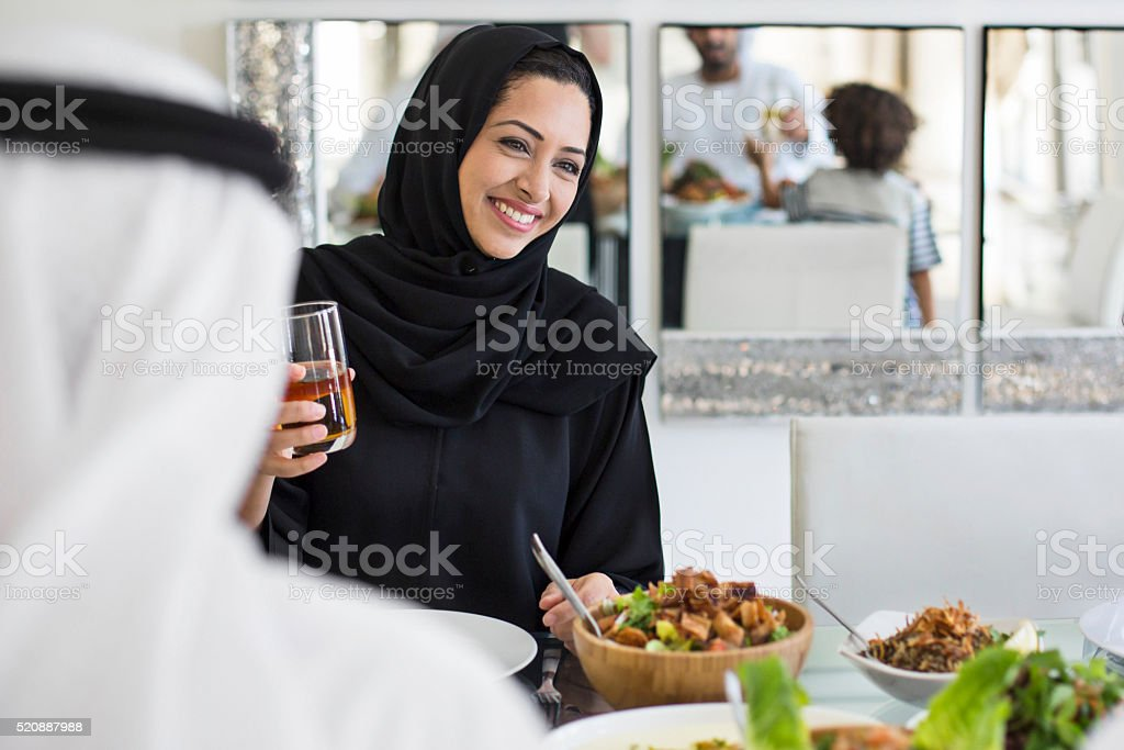 Happy Middle Eastern woman eating with family stock photo