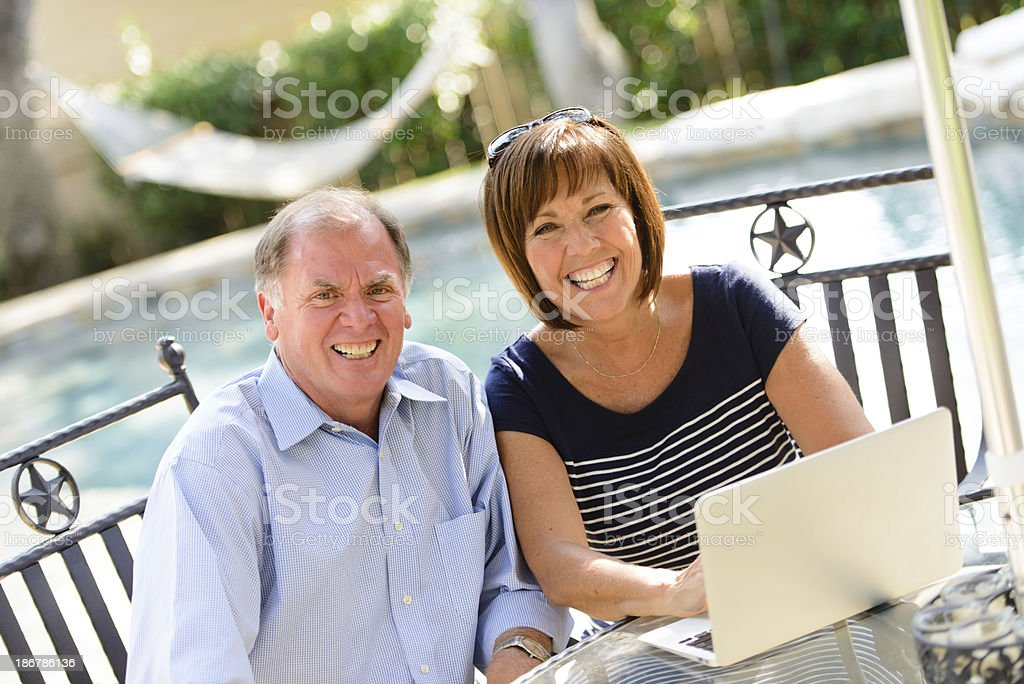 Happy Middle-Age Couple Using Technology at the Pool royalty-free stock photo