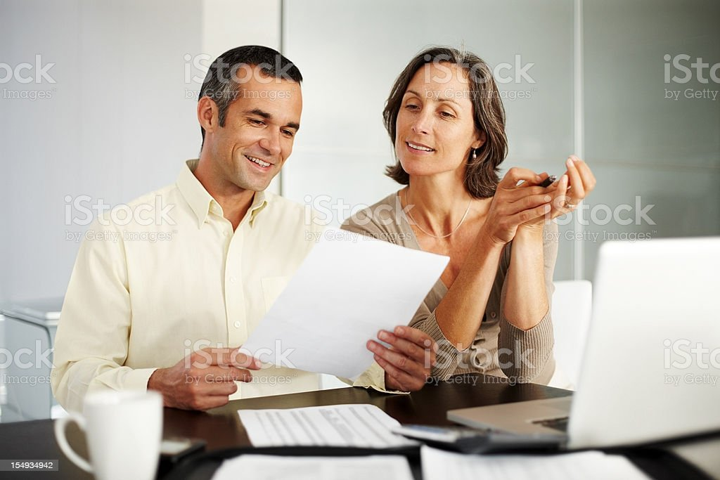 Happy, middle-aged couple working on financial expenses royalty-free stock photo