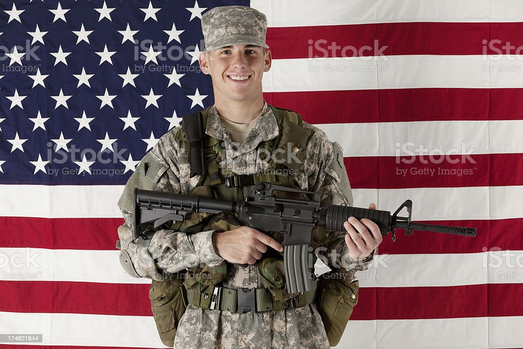 Happy military man posing in front of American flag royalty-free stock photo