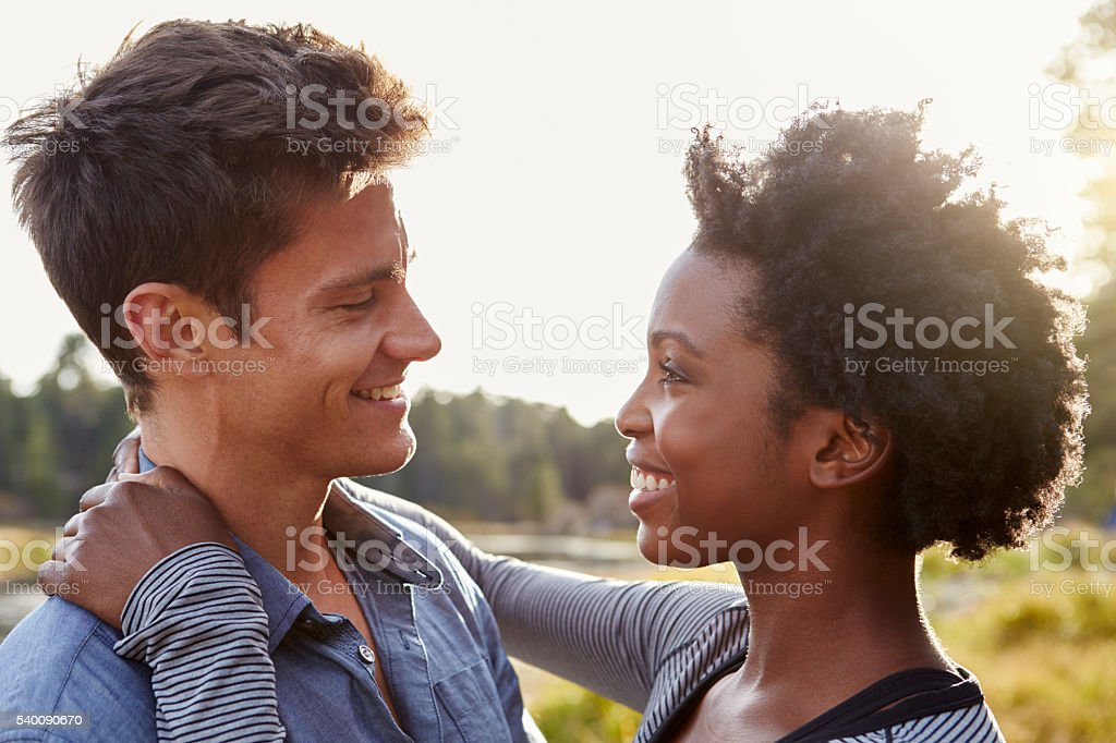 Happy mixed race couple embracing in the countryside stock photo