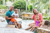 Happy mixed race family at resort swimming pool