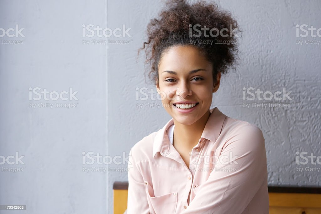 Happy mixed race woman smiling indoors stock photo