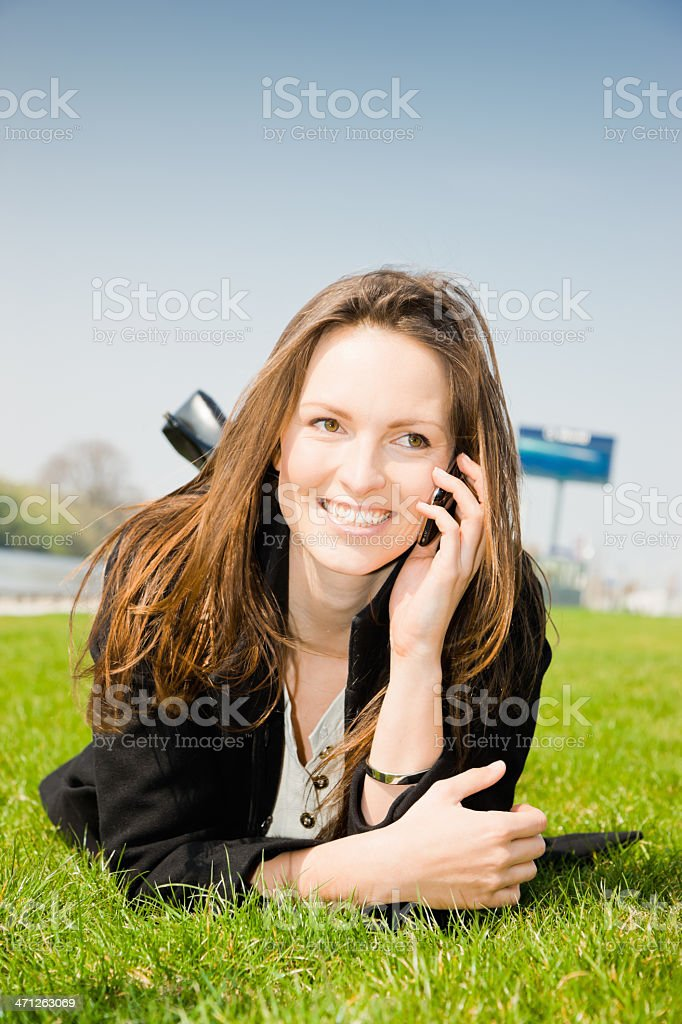 Happy Mobile Phone Call Young Woman Lying on Grass royalty-free stock photo