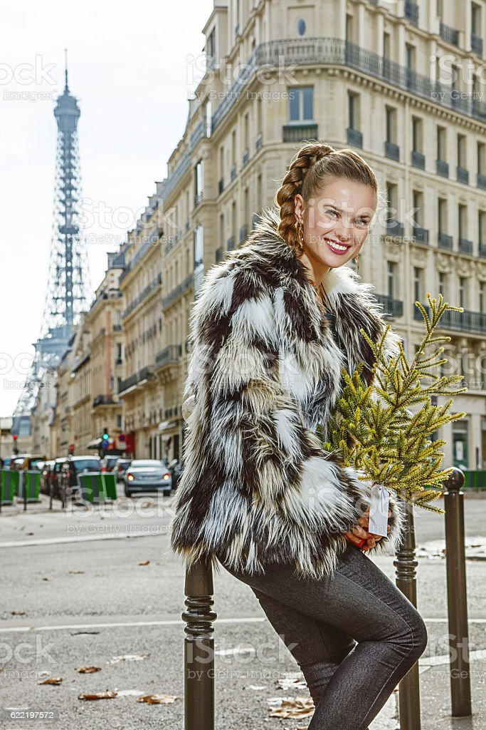 happy modern fashion-monger with Christmas tree in Paris, France stock photo