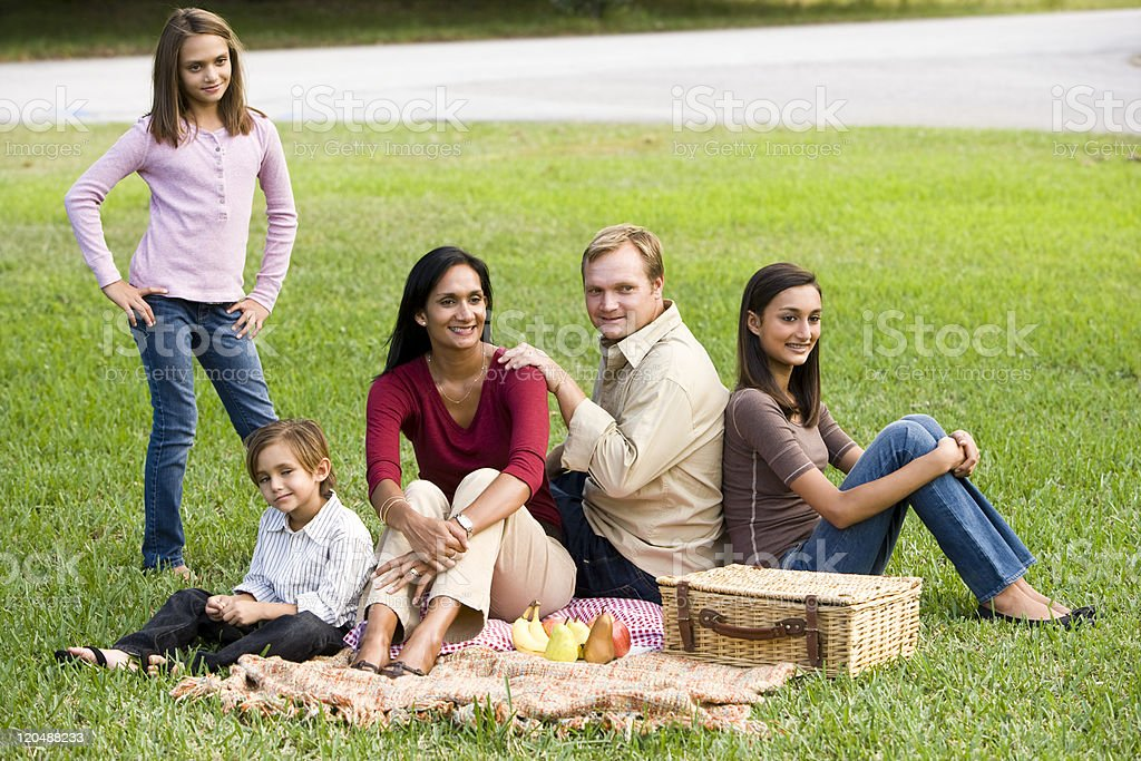 Happy modern multicultural family enjoying a picnic royalty-free stock photo