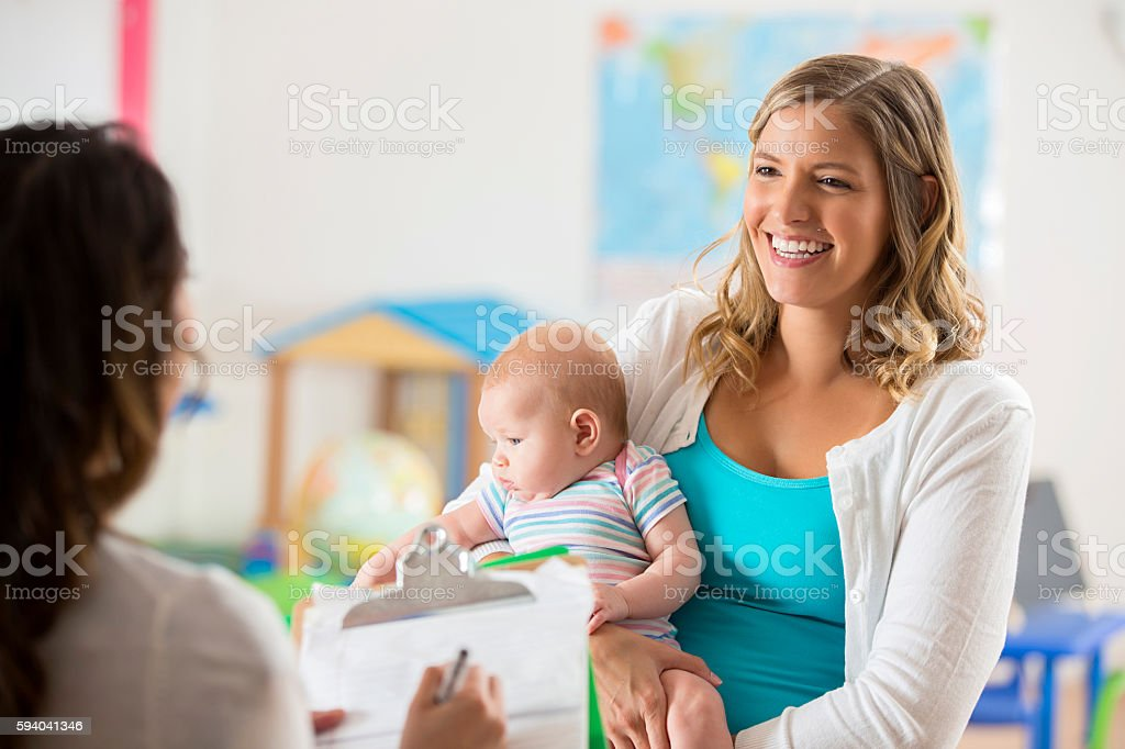 Happy mom and baby getting tour of a daycare center stock photo