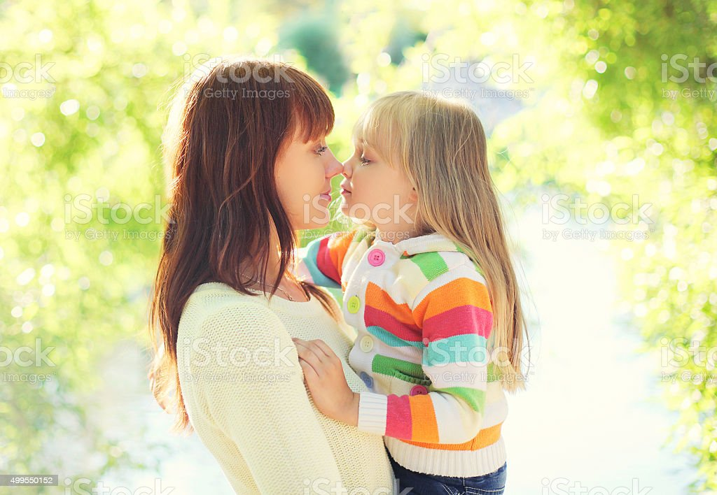 Happy mom and child together in sunny summer day stock photo