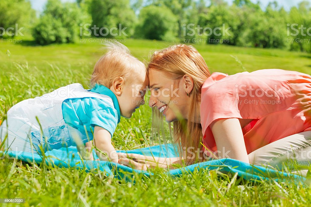 Happy mom and child with foreheads close together stock photo