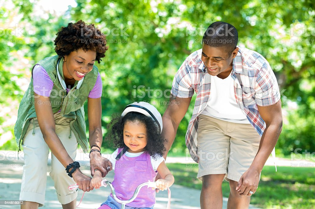 Happy mom and dad teaching daughter to ride tricycle stock photo