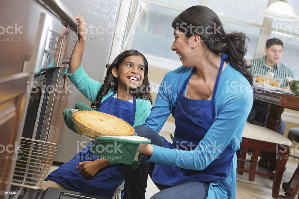 Happy mom and daughter baking together in modern kitchen stock photo